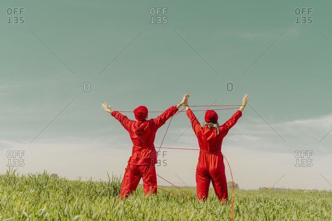 Back view of young couple wearing red overalls and hats performing on a field with red string