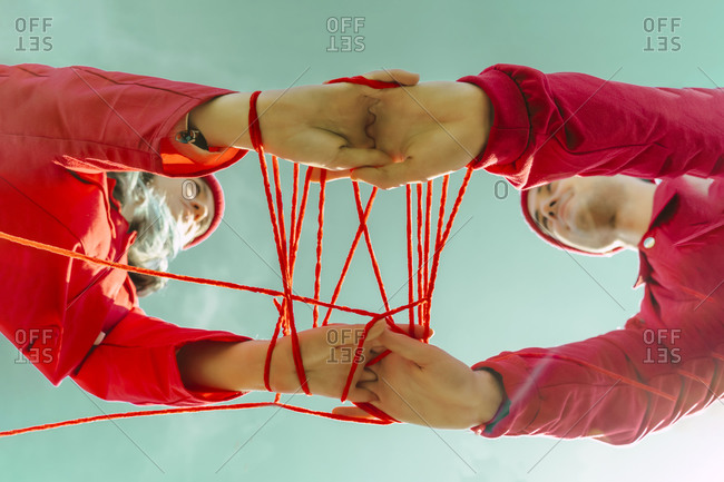 Crop view of young couple dressed in red performing with red string against sky