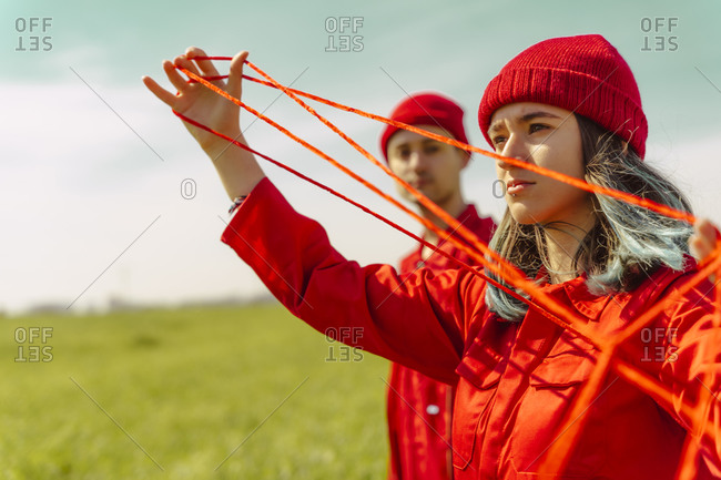 Portrait of young woman dressed in red performing with red string outdoors