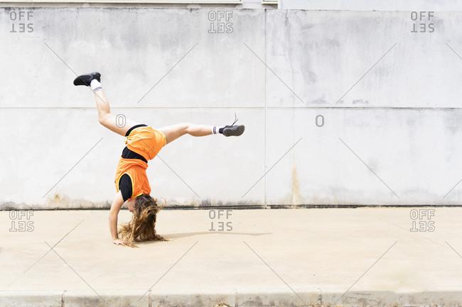 Teenage girl doing acrobatics outdoors