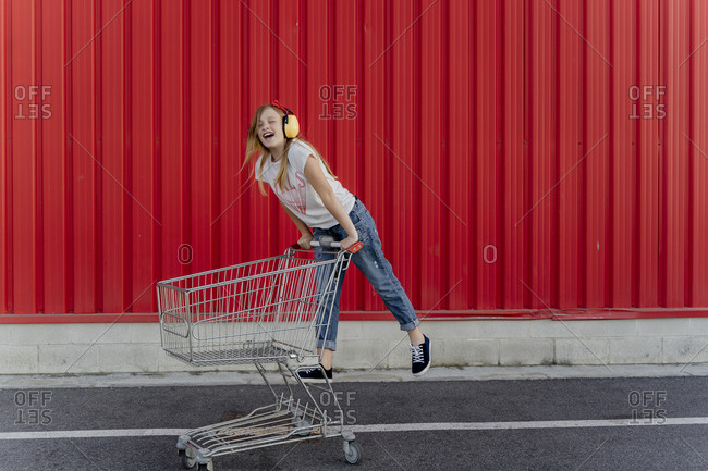 Girl with a shopping cart and ear defender in front of red wall