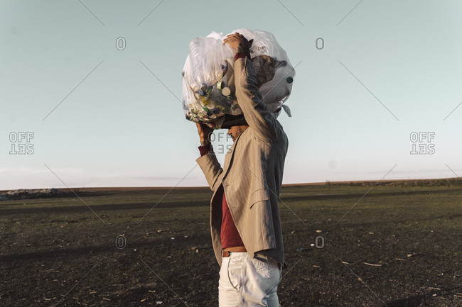 Young man carrying bag with plastic bottles on his head in barren land