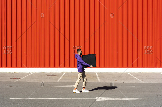 Young man carrying a box in front of a red wall