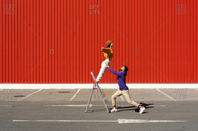 Young man and woman performing with a ladder in front of a red wall