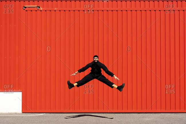 Smiling man dressed in black jumping in the air in front of red roller shutter