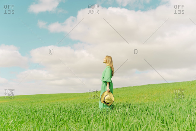 Blond young woman wearing green dress standing on a field