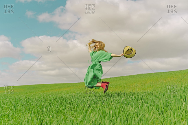 Happy young woman wearing green dress jumping in the air on a field
