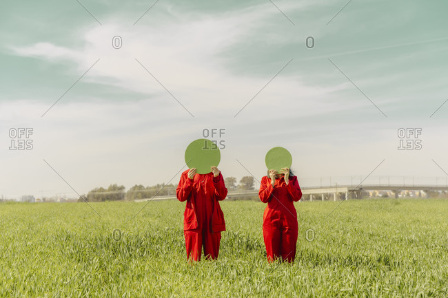 Young couple wearing red overalls standing on a field hiding faces behind green circle