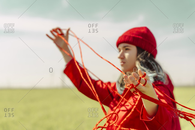 Young woman dressed in red performing with red string outdoors