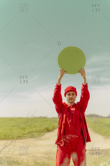 Portrait of young man dressed in red holding green circle