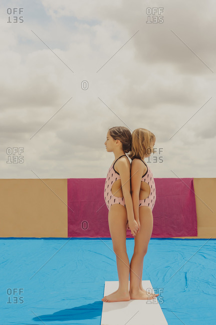 Two girls wearing swimsuits standing back to back with eyes closed outdoors