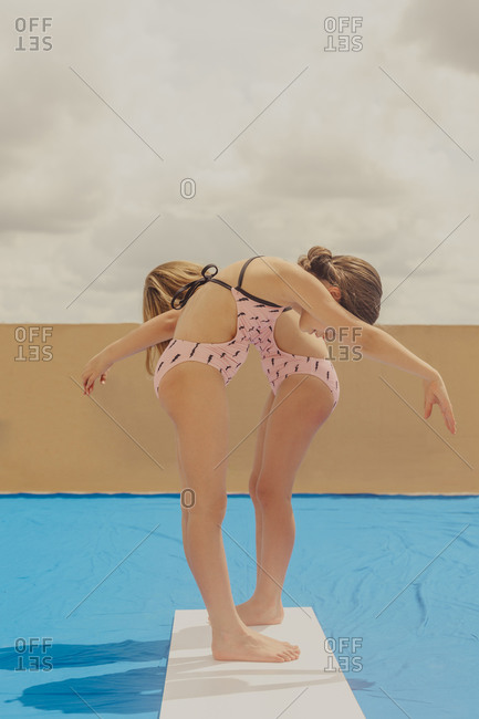 Two girls playing swimming pool on roof terrace