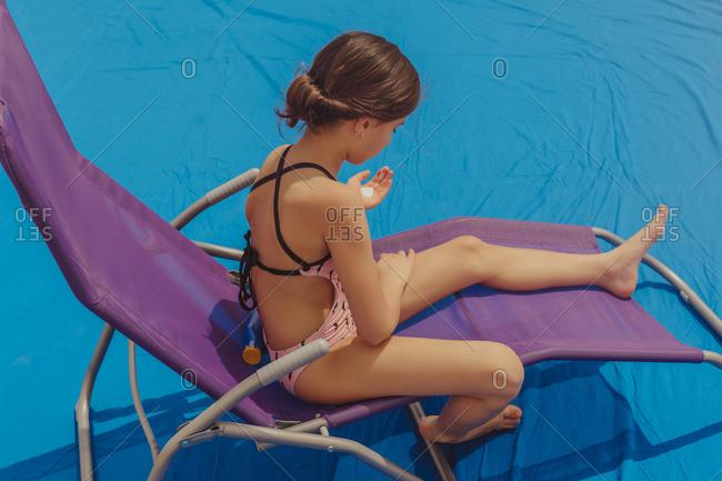 Girl sitting on sun lounger applying sun cream
