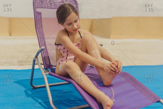 Portrait of girl sitting on sun lounger applying sun cream