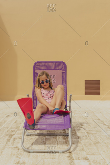 Portrait of girl wearing sunglasses- swimsuit and diving flippers sitting on beach lounger on roof terrace