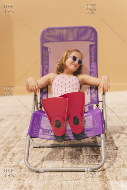 Girl lying on beach lounger on roof terrace diving flippers