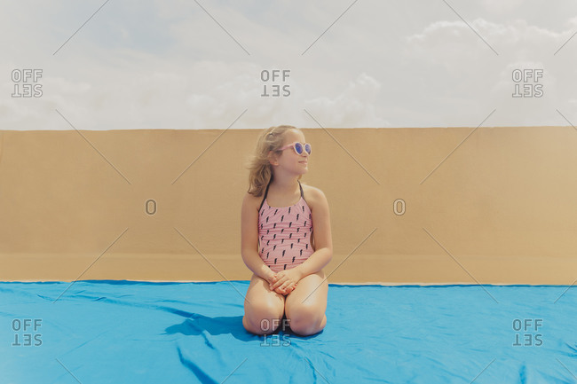 Smiling girl wearing pink sunglasses and swimsuit sitting on roof terrace