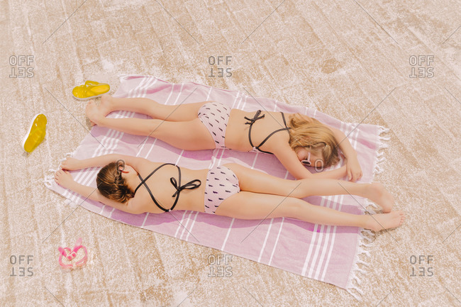 Two girls in swimsuits lying on blanket relaxing