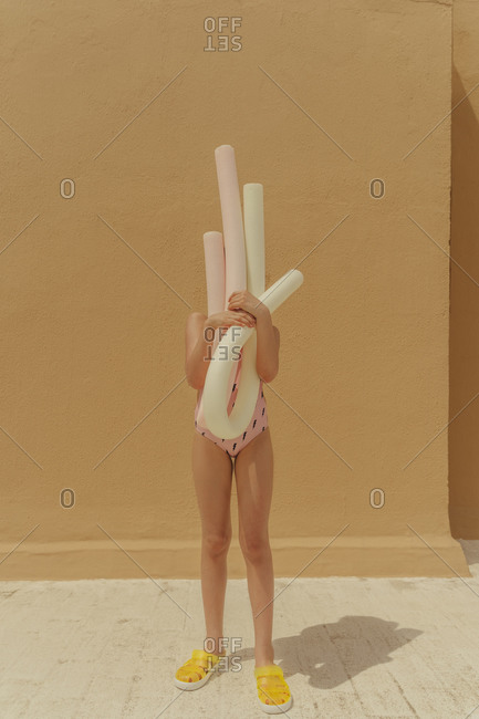 Girl in swimsuit hiding her face behind pool noodles