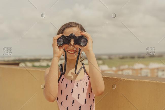 Portrait of smiling girl in swimsuit standing on roof terrace looking through binoculars