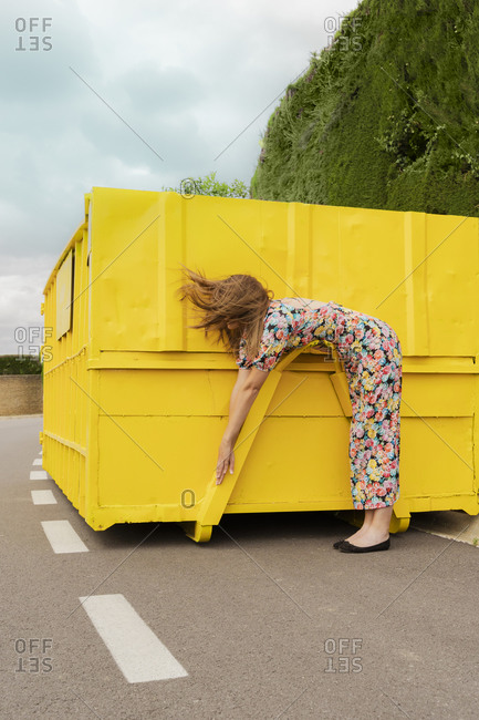 Woman in flower dress bending over attachment of yellow container