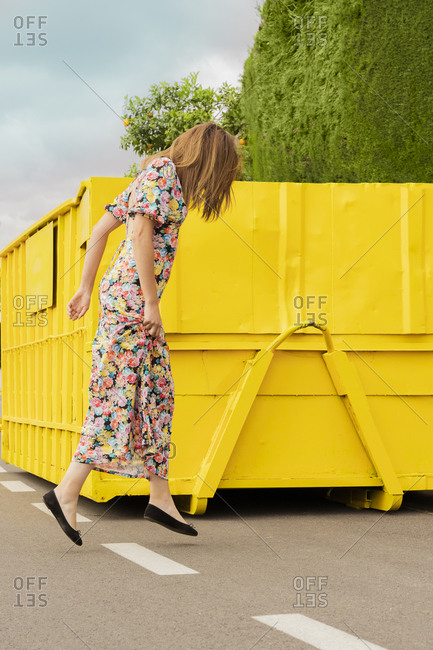 Woman in flower dress- jumping in the street in front of yellow container