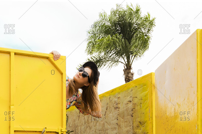Curious woman looking out of yellow container