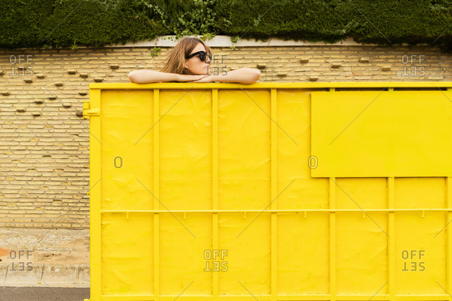 Woman wearing sunglasses- leaning on edge on yellow container