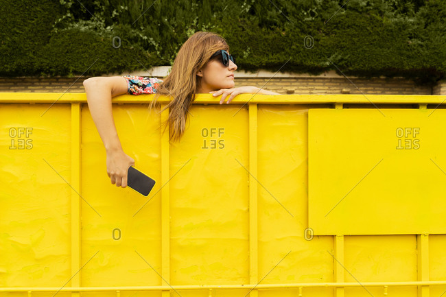 Woman wearing sunglasses- leaning on edge on yellow container- holding smartphone