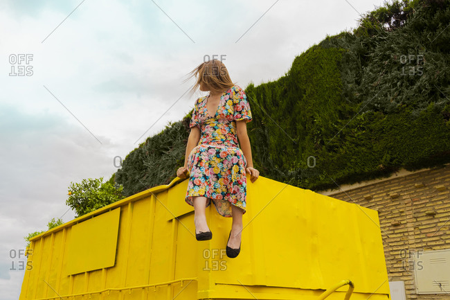 Woman in flower dress sitting on edge of yellow container