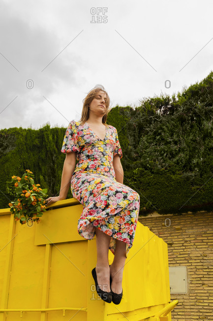 Woman in flower dress sitting on edge of yellow container- holding bunch of flowers