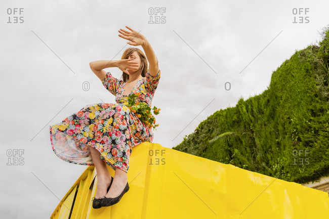 Woman in flower dress sitting on edge of yellow container with bunch of flowers in her lap- moving arms