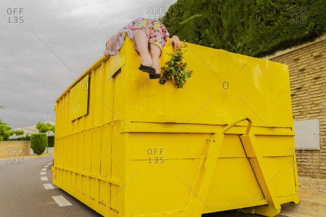 Woman lying on top of yellow container- holding Buch of flowers