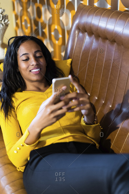 Smiling woman lying on couch in vintage living room using cell phone