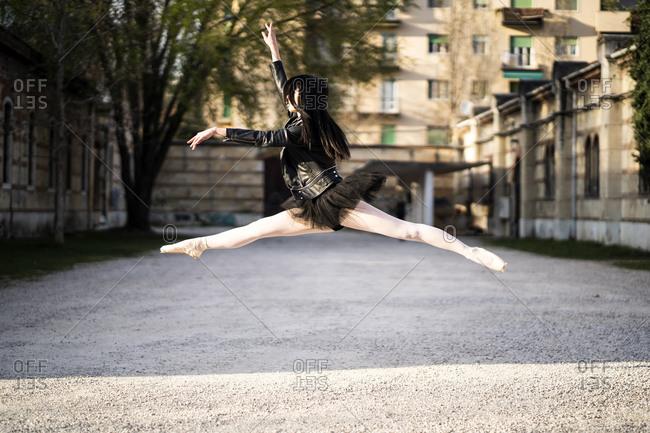 Italy- Verona- Ballerina wearing leather jacket and tutu jumping midair