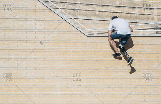 Young man with leg prosthesis climbing up brick wall