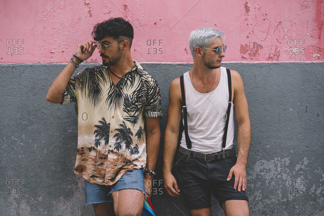 Gay couple looking sideways in front of pink and grey wall
