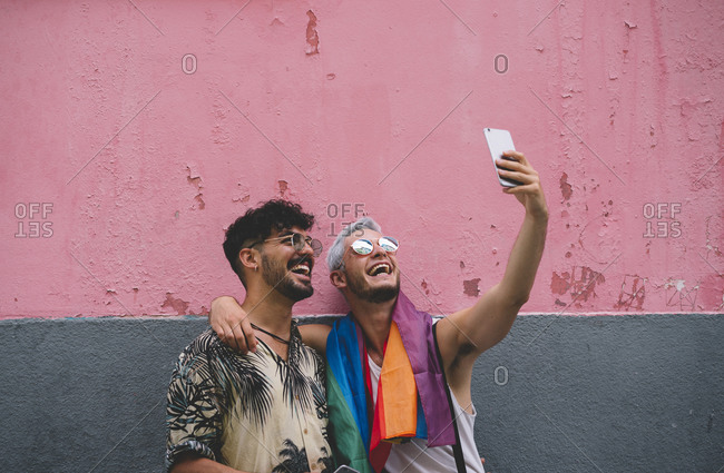 Gay couple taking a selfie in front of pink and grey wall