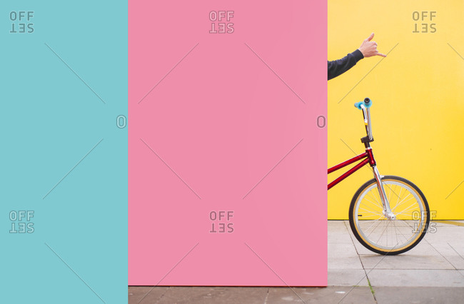 Boy with BMX bike- hiding behind pink wall-making Rock's Roll sign