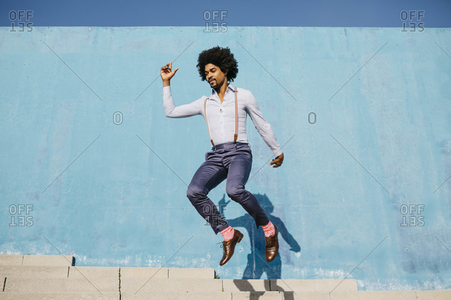 Stylish man jumping in the air in front of blue wall