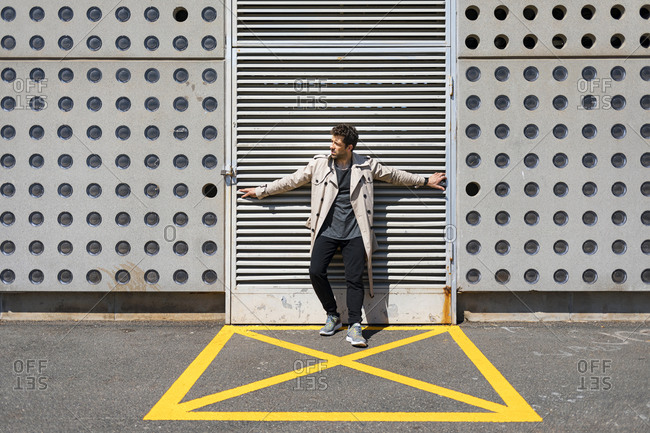 Mid adult man standing in yellow marked area in front of concrete wall- with arms outstretched