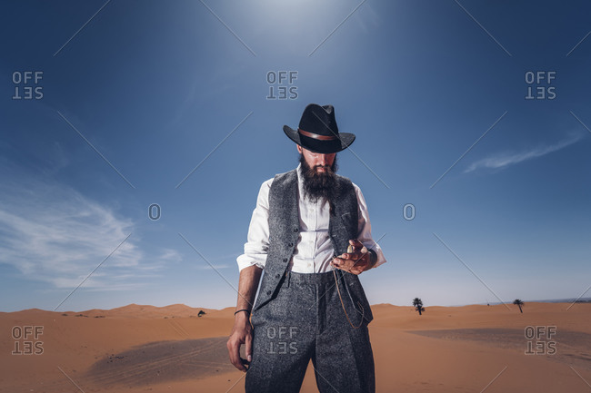 Man with a beard and hat in the dunes of the desert of Morocco checking the time