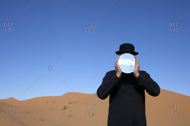 Morocco- Merzouga- Erg Chebbi- man wearing a bowler hat holding mirror in front of his face in desert dune