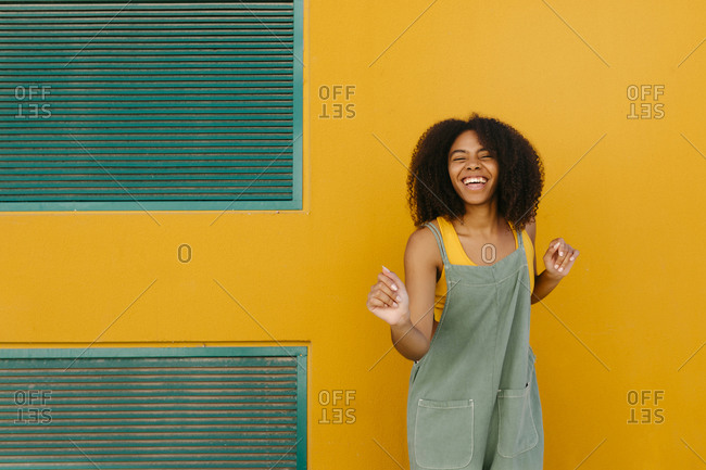 Portrait of happy young woman wearing overalls in front of yellow wall