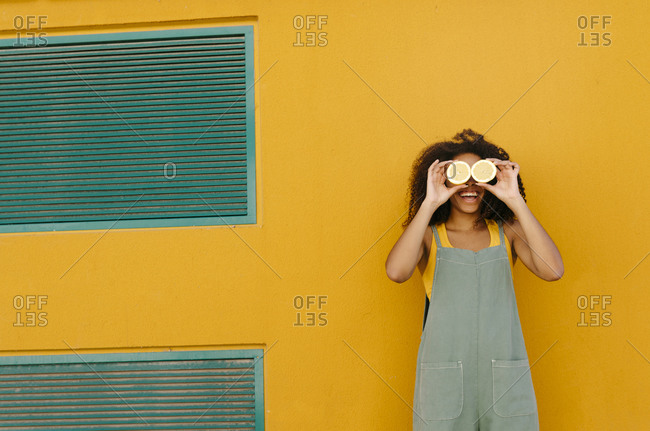 Happy young woman wearing overalls in front of yellow covering her eyes with lemons