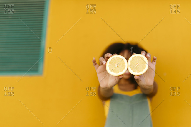 Close-up of young woman holding halved lemons