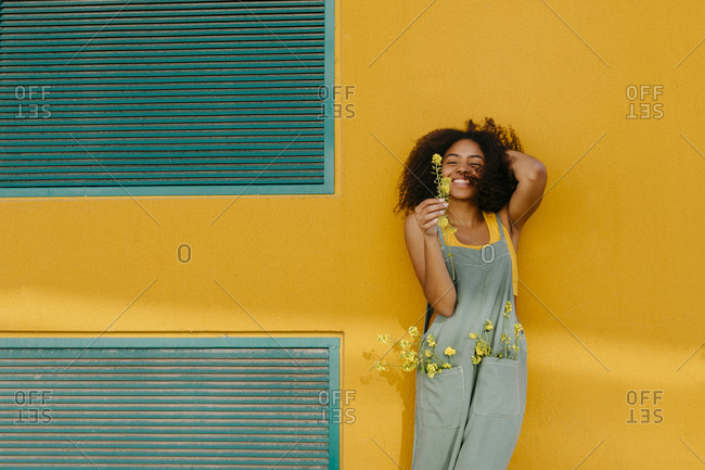 Portrait of happy young woman wearing overalls holding flowers in front of yellow wall