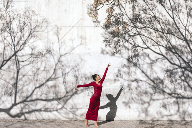 Woman in red dress with dancer pose and tree shadows on wall
