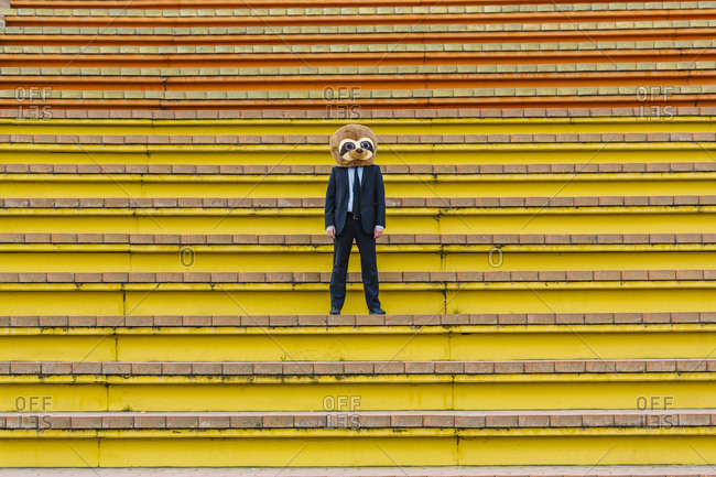 Businessman in black suit with meerkat mask standing on stairs