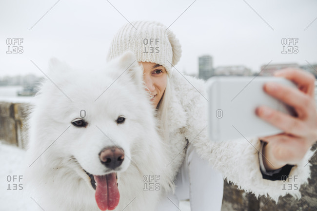 Serbia- Petrovaradin- white dressed woman taking selfie with white dog in winter